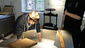 Angehender Gestaltungstechnischer Assistent beim Papier schöpfen.