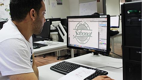 Erst vorzeichnen, dann am PC gestalten: Ein angehender Mediengestalter Digital und Print bei der Arbeit.