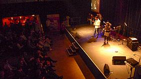 Moderatorin und Moderator vor Publikum.