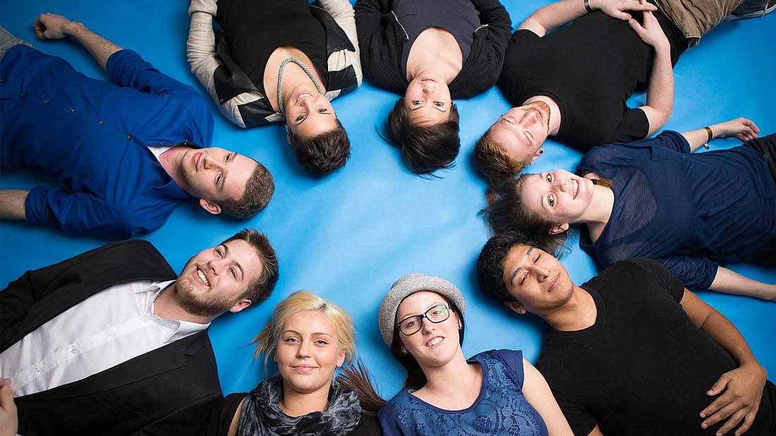 Teilnehmer der Berufsakademie für Medienberufe bilden einen Kreis.