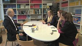 Schülerinnen sitzen mit einem Lehrer am Tisch und unterhalten sich.