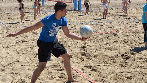 Junger Sportler beim Beachvolleyball.
