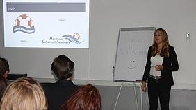 Junge Frau präsentiert Logo-Entwürfe.